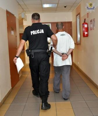 Starogard Gdański - Aresztowano sprawców rozboju. policjant prowadzi zatrzymanego (1)